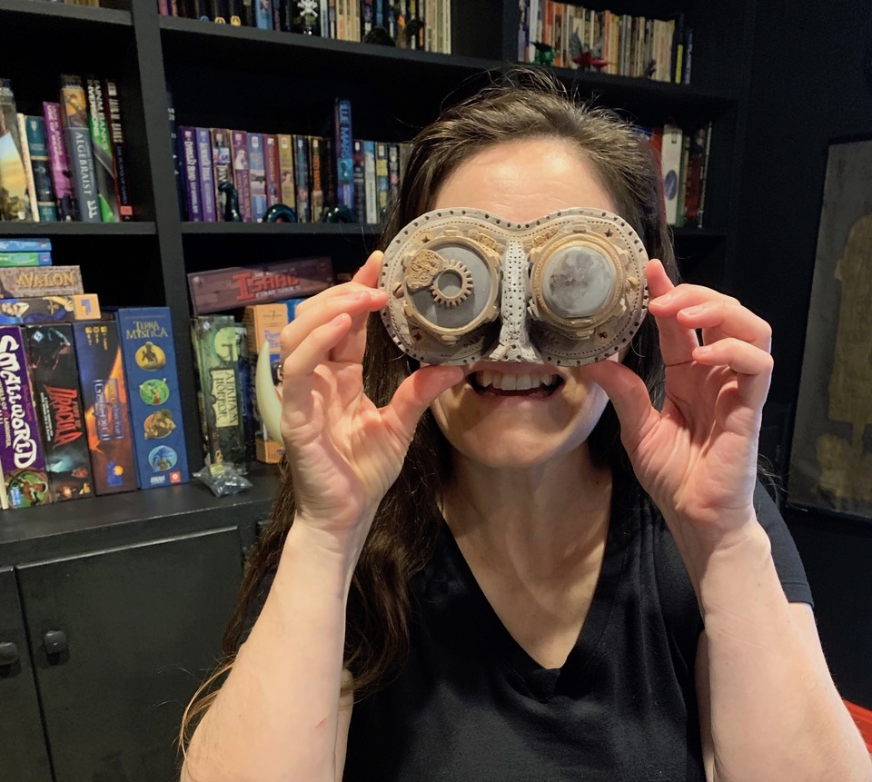 Andrea holding chocolate steampunk goggles to her face.